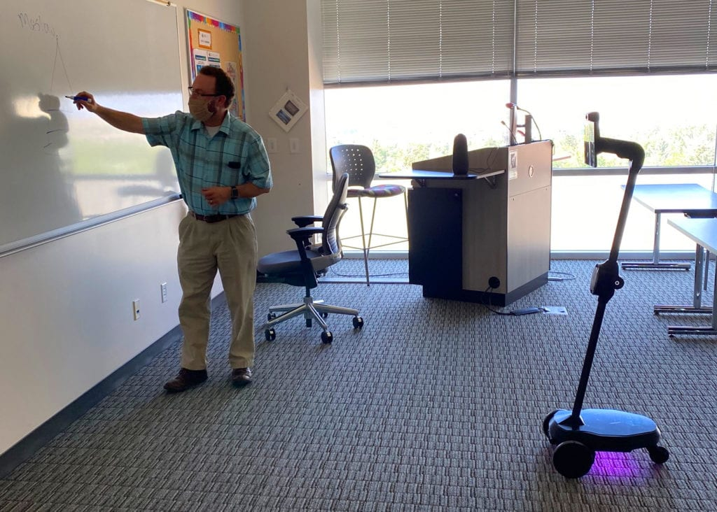 Faculty member R. Paul Maddox uses one of the two Ohmni robots in the classroom
