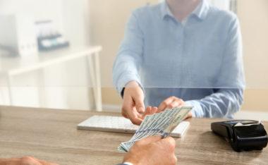Bank teller receives money for deposit