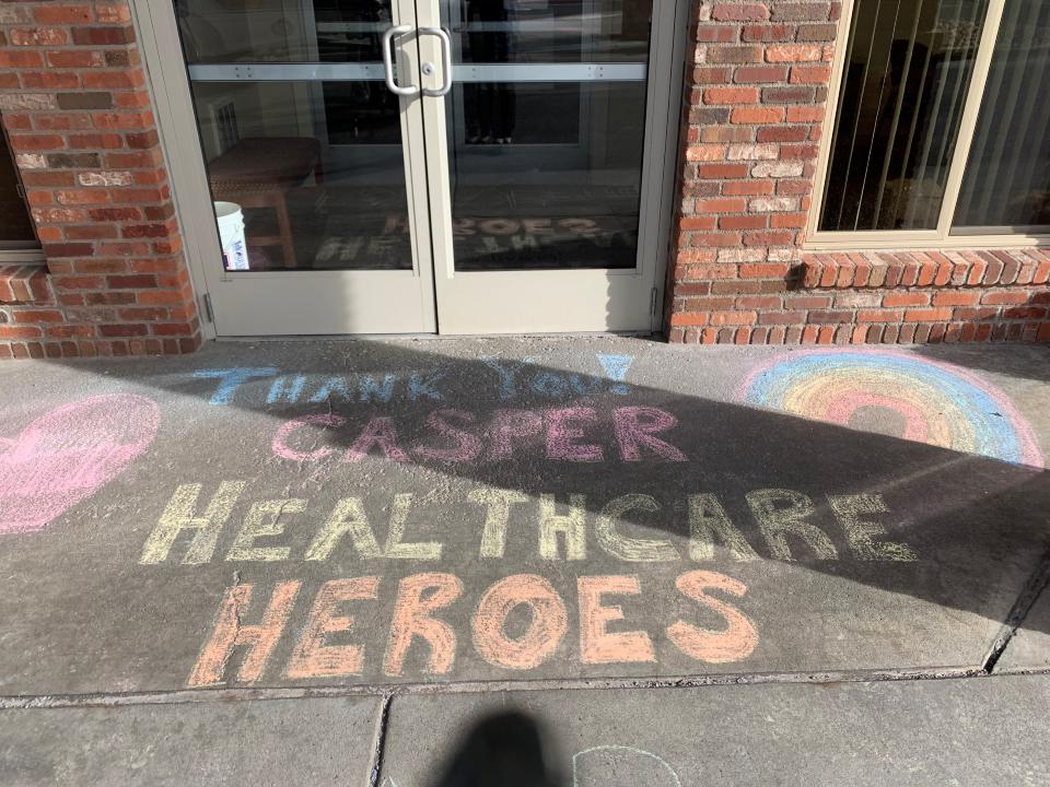 Thank you Healthcare Heroes is written on the sidewalk in chalk