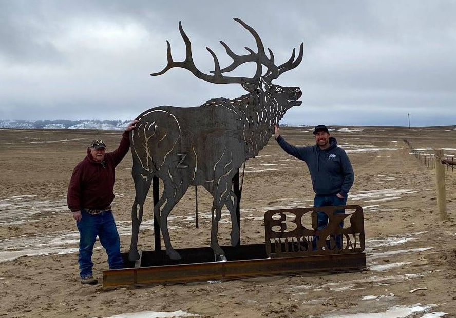 Two men stand next to elk metal silhouette